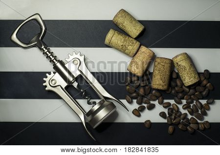 Nut, corkscrew and corks from wine bottles on a black and white background