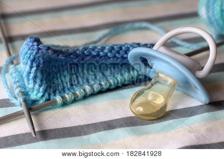 Children's pacifier and knitting needles. Prepared for the birth of a child.