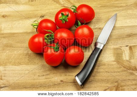 Several small red tomatoes and a knife lie on a wooden surface