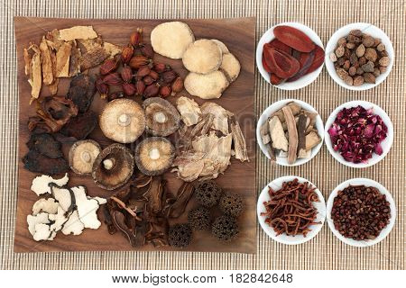 Chinese herb selection used in natural herbal medicine on maple wood board and in porcelain on bamboo background.