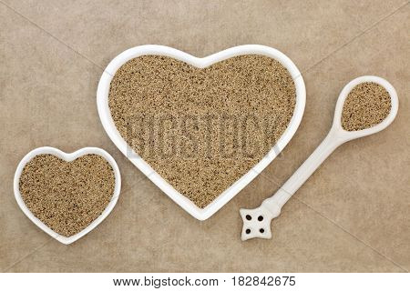 Teff super grain health food in heart shaped porcelain dishes and spoon on hemp paper background.