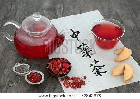 Pomegranate flower herb tea in a glass cup with metal strainer and fortune cookies on rice paper with calligraphy script. Translation reads as chinese herb tea.