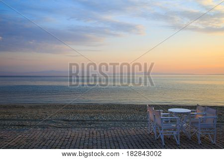 Table and chairs in the bar Early morning at dawn of the day with a calm blue sea overlooking the sky and mountains of the other shore Kassandra Greece