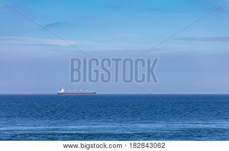 Large cargo tanker sailing across a blue sea horizon