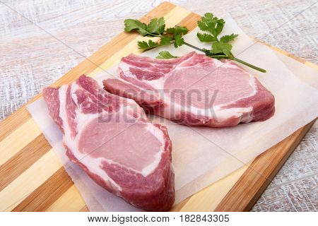 Raw pork chops, spices and basil on cutting board. Ready for cooking