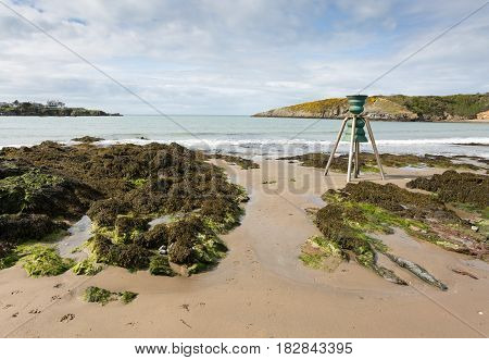 Cemaes bay in Anglesey North Wales at low tide with tidal bell