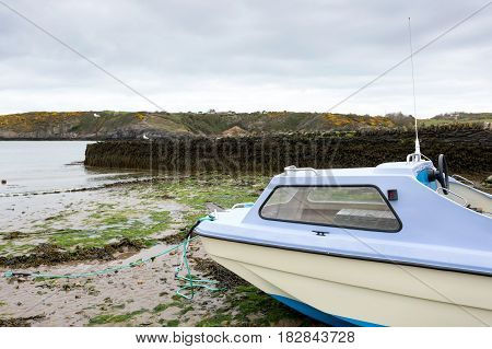 Small fishing dingy moored at low tide