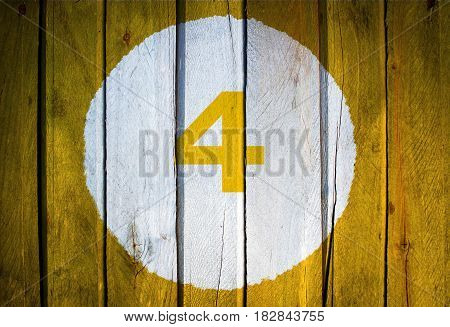 House Number Or Calendar Date In White Circle On Yellow Toned Wooden Door Background. Number Four 4