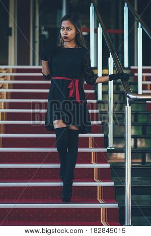 Young elegant woman in black dress walking on stairs with the red carpet