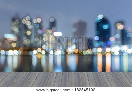 Opening wooden floor City blurred bokeh light office building with reflection at twilight abstract background