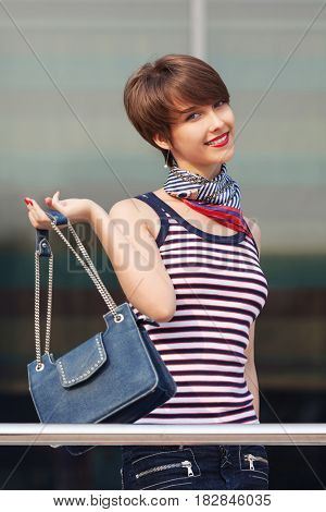Happy young fashion woman with handbag next to mall windows