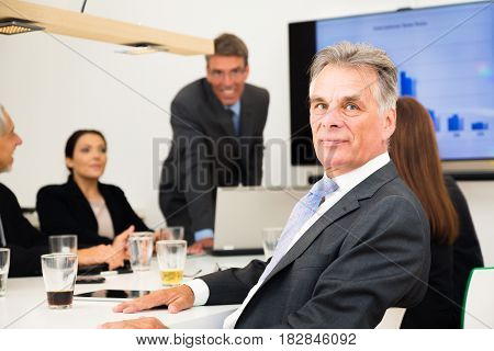 business team sitting in conference room, looking at a presentation. the manager is looking at the camera.