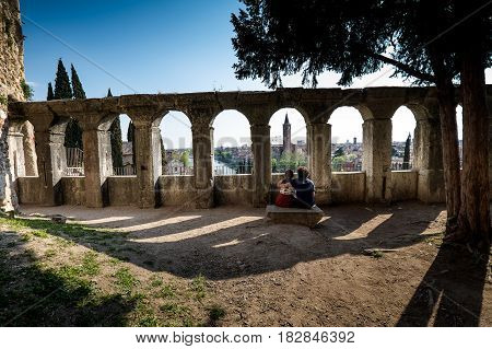 VERONA, Italy - April 04, 2017: Amphitheater of the Teatro Romano in Verona, Italy, lovers and view of the city from roman arches