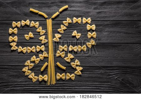 A butterfly made of three types of durum wheat pasta on a black wooden table background