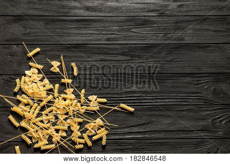 Three types of durum wheat pasta on a black wooden table background