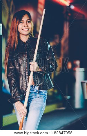Young beautiful girl wearing leather jacket in a billiard club with cue stick preparing for the game