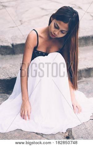 Young beautiful girl in white long dress sitting on the concrete floor