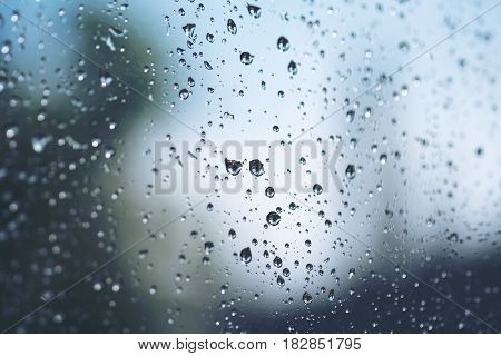Raindrops outside the window with green nature background