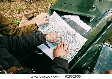 Pribor, Belarus - April 23, 2016: Re-enactor Dressed As Russian Soviet Crew Member Tank Commander Soldier Of World War Ii Briefs, Showing Direction Of A Platoon Attack On Map Lying On Hood Of Armored Soviet Scout Car In Forest.