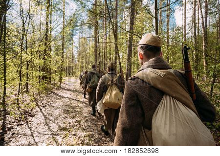Group Of Re-enactors Dressed As Soviet Russian Red Army Infantry Soldiers Of World War II Marching Along Forest Road At Spring Season.