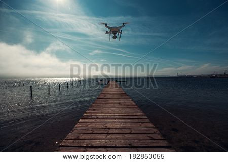 Beautiful morning over the sea. Pier on the foreground and flying drone.