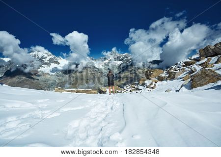 hiker at the top of a pass with backpack enjoy sunny day in Alps. Switzerland, Trek near Matterhorn mount.
