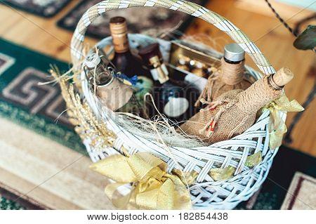 Wine bottles in a basket on a floor.