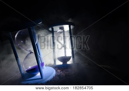 Time Concept. Silhouette Of Hourglass Clock And Smoke On Dark Background With Hot Yellow Orange Ligh