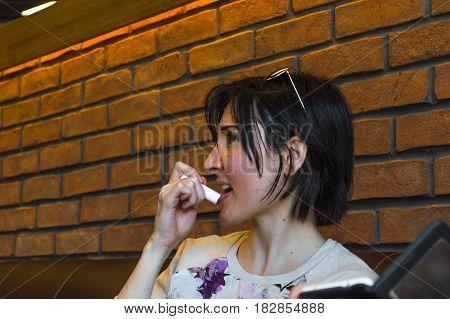 Beautiful Brunette Young Woman Applying Lip Balm On Her Lips