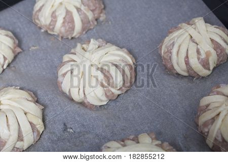 Meatballs Wrapped In Strips Of Puff Pastry Lie On A Baking Sheet.