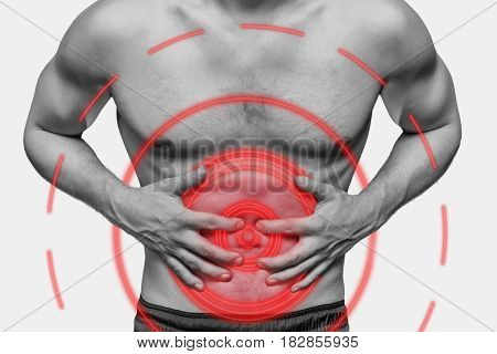 Unrecognizable man compresses his abdomen due to acute pain. Monochrome image isolated on a white background. Pain area of red color.