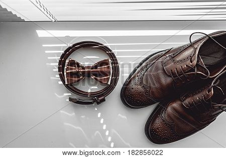 Brown bow tie, leather shoes and belt. Grooms wedding morning. Close up of modern man accessories on the window sills with shutters. Look from above