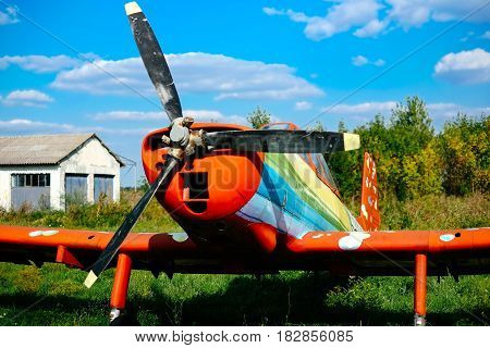 Colorful airplane parked on the grass at the airfield