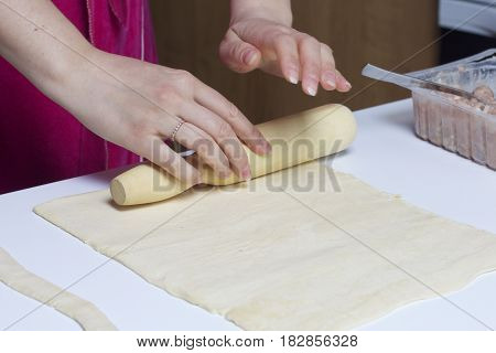 Stages Of Preparation Of Meat Glomeruli. A Woman Rolls Out The Dough. Next To The Table Is A Stuffin