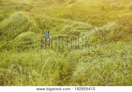 Explorer young woman walking on footpath among summer meadows image with tilt-shift effect.