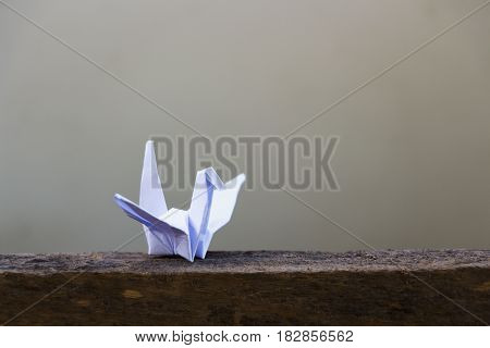Paper bird on a wooden floor for peace.