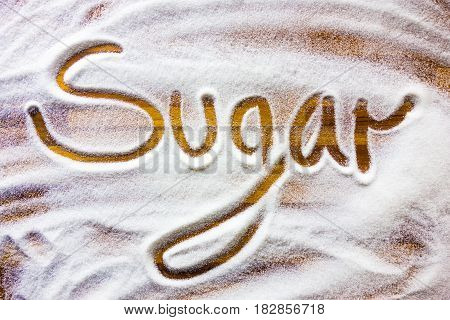 Word sugar written ontop sugar background wooden table