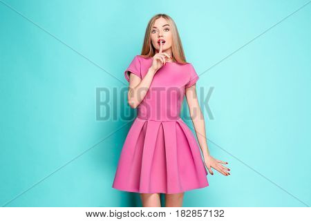Smiling beautiful young woman calling for silence in pink mini dress posing and looking at camera. Three quarter length studio shot on blue background.