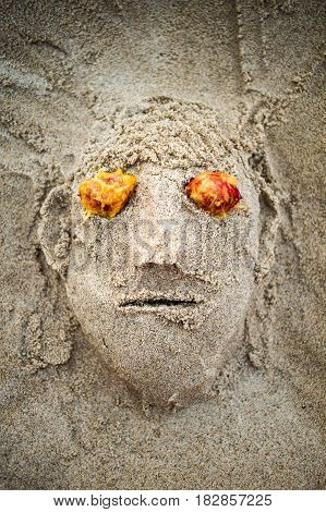Sand Face Made On Beach With Red Eyed Made Of Fruit Stones