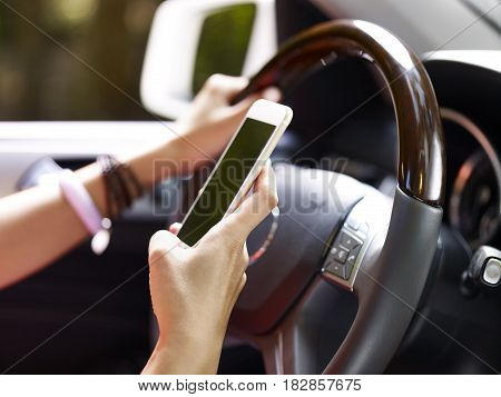 hands of female holding cellphone and steering wheel inside a vehicle.