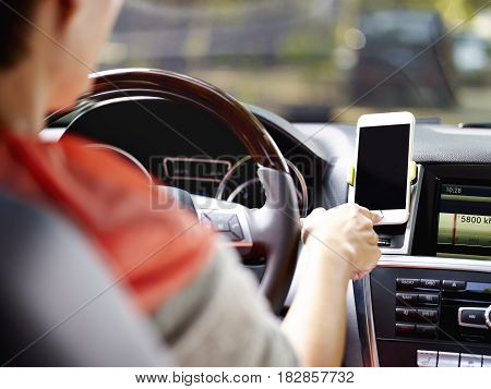female driver using cellphone to navigate before driving.
