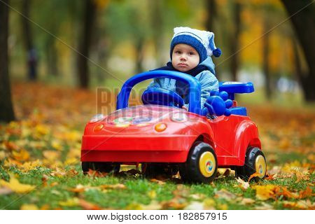 photo of little funny boy driving toy car