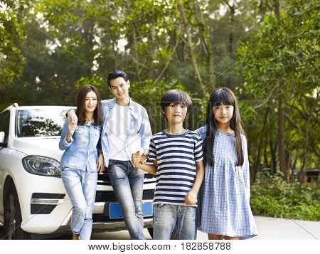 asian family with two children traveling by car.