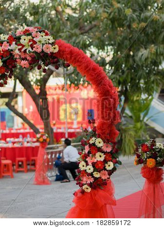 COLOR PHOTO OF WEDDING ENTRANCE DECORATED WITH FLOWERS