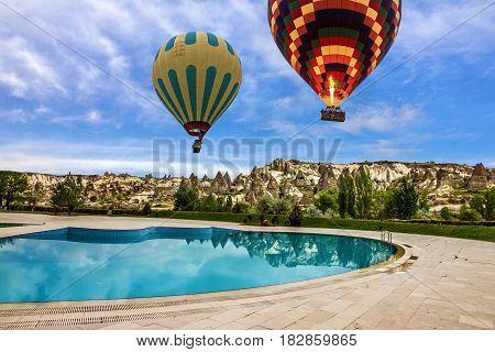 Hot air balloons over swimming pool, Cappadocia, Turkey