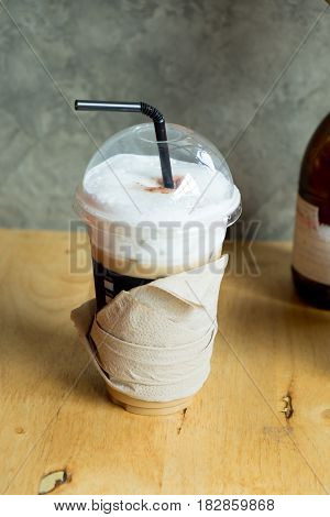 Cold coffee in plastic cup on brown wooden table at cafe