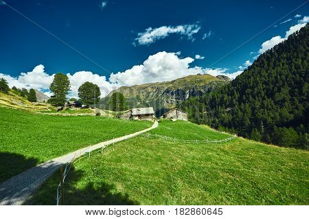 Alpine meadow with houses at afternoon, around Zermatt