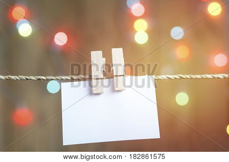 paper holding on rope for present and write your words with bokeh background