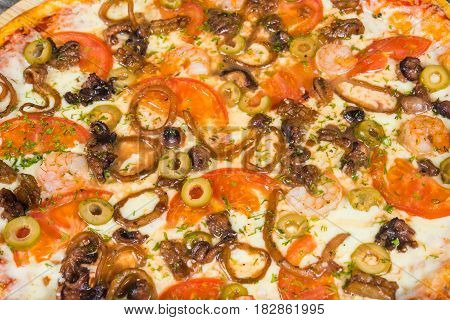 Pizza with seafood, with rosemary and spices on a light wooden background. Italian pizza on a background of green basil and fresh vegetables