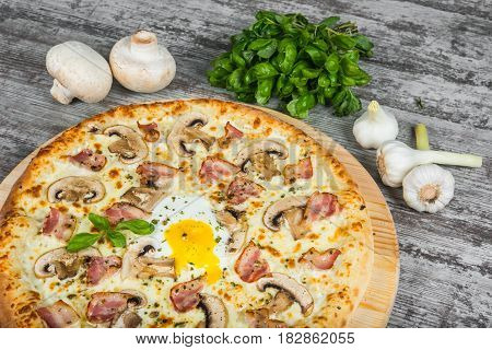 Pizza With Bacon, Mushrooms And Egg, With Rosemary And Spices On A Light Wooden Background. Italian